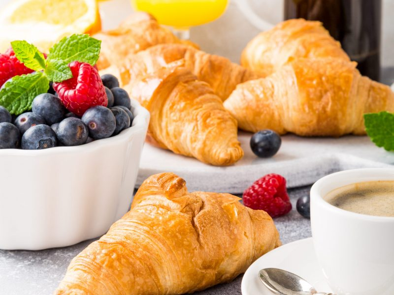 Delicious continental breakfast with fresh flaky croissants, assorted preserves, orange juice and coffee, close up on the croissant.