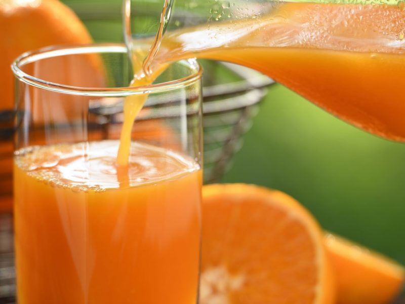 Pouring fresh orange juice in glass with sliced orange on nature background